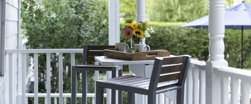Small table for two with two high chairs and a tray with tea and flowers